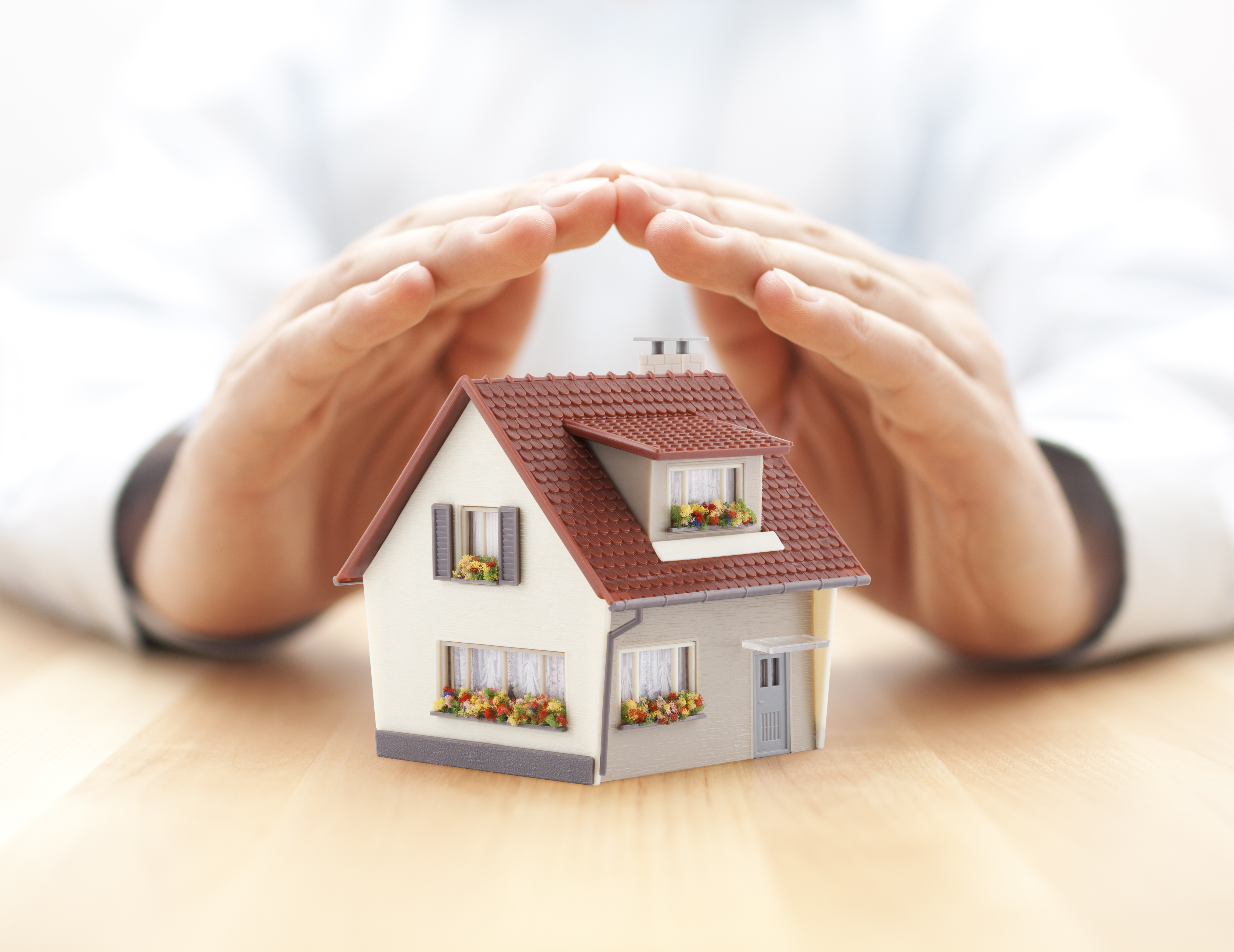 Small toy house covered by hands